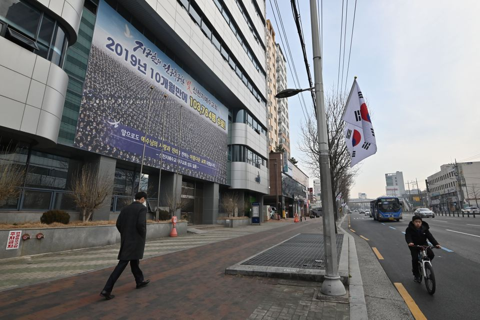 A man wearing a face mask walks in front of the Daegu branch of the Shincheonji Church of Jesus in the...