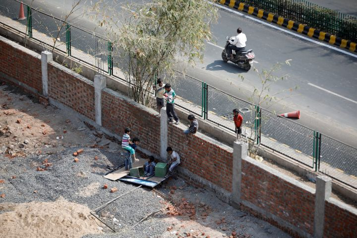 Children play on a wall that was built along a slum area as part of a beautification drive along a route that U.S. President Donald Trump and India's Prime Minister Narendra Modi will be taking during Trump's visit.