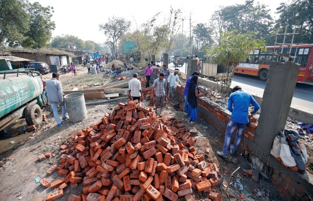 Construction workers build a wall along a slum area as part of a beautification drive along a route that...