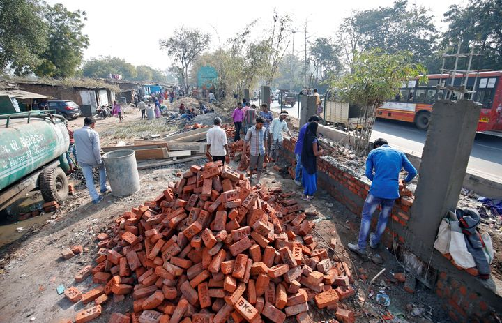 Construction workers build a wall along a slum area as part of a beautification drive along a route that U.S. President Donald Trump and Prime Minister Narendra Modi will be taking during Trump's visit.