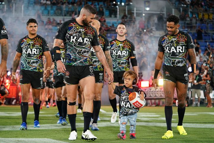 Quaden Bayles leads the Indigenous All Stars on to the field with captain Joel Thompson prior to the NRL Indigenous All-Stars vs. Maori Kiwis match at CBus Super Stadium on the Gold Coast.