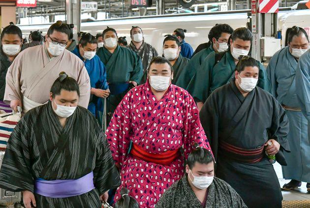 In this Sunday, Feb. 23, 2020, photo, sumo wrestlers wearing masks arrive at Shin Osaka railway station...