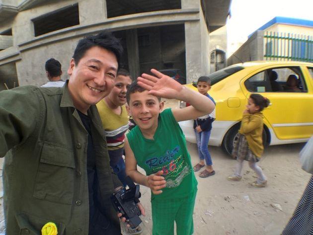 パレスチナのガザ地区で少年と一緒に撮影する堀潤さん