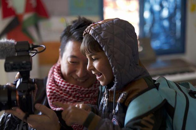 ヨルダン・ザアタリ難民キャンプで、カメラに興味を持つ少年と笑顔を見せる堀潤さん