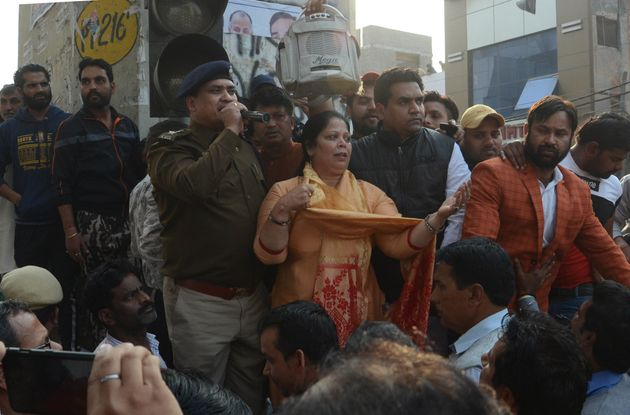 A police personnel addresses the crowd in the presence of BJP leader Kapil Mishra, at Maujpur, on Sunday...