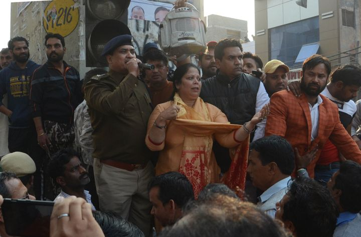 A police personnel addresses the crowd in the presence of BJP leader Kapil Mishra, at Maujpur, on Sunday in New Delhi.
