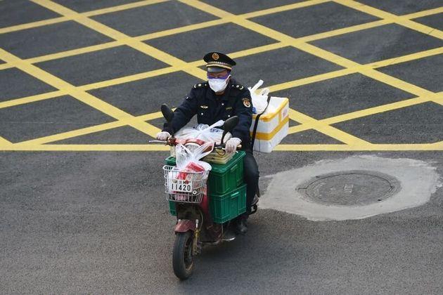 Un hombre con una máscara conduce su motocicleta con alimentos en