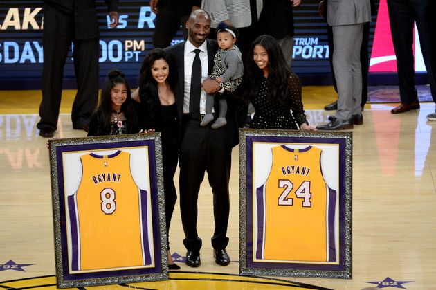 Kobe Bryant poses with his family after both his Los Angeles Lakers jerseys, numbers 8 and 24, are retired...