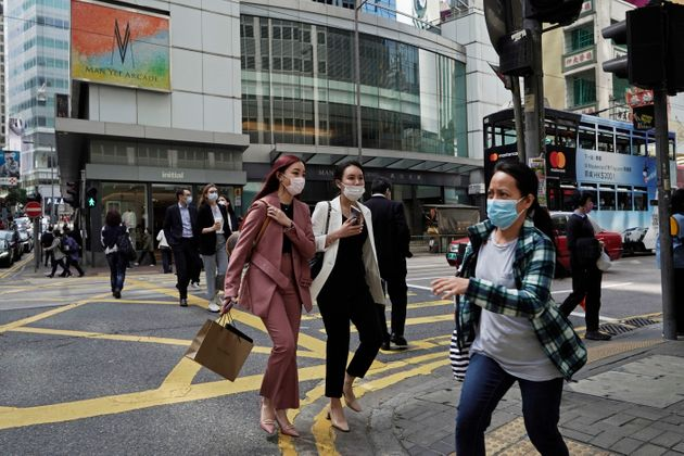 People wearing masks walk across a street in Hong Kong on Monday. COVID-19 has sickened thousands of...