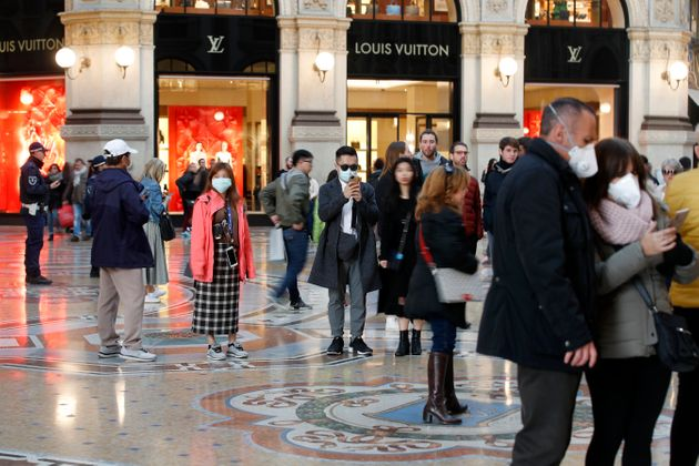 Tourists wearing sanitary masks walk in downtown Milan, Italy, on Sunday. The country has reported Europe's...