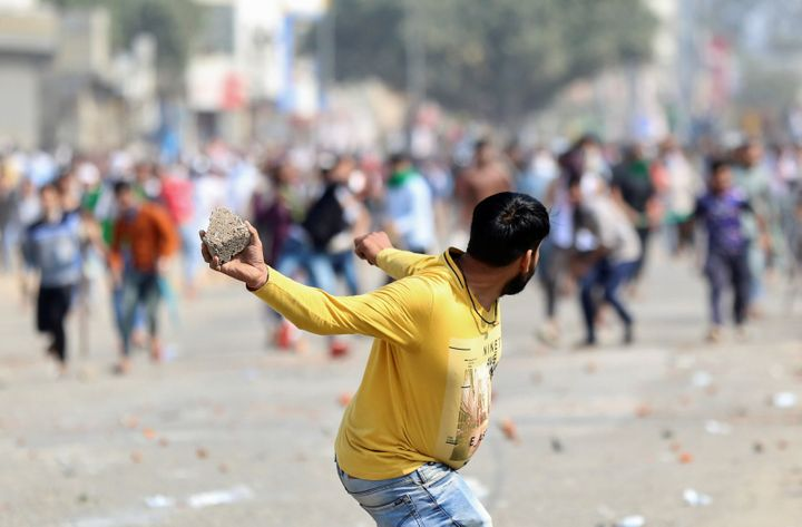 A man supporting the new citizenship law throws a stone at those who are opposing the law, during a clash in New Delhi, February 24, 2020.