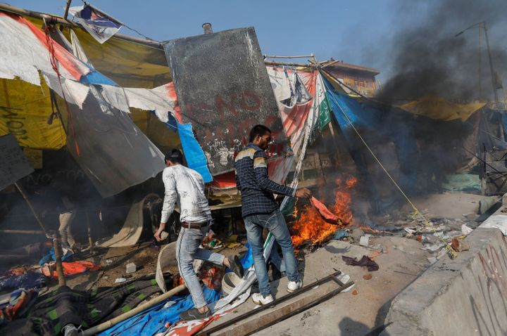 People supporting the new citizenship law destroy the protest site used by those opposing it, in New Delhi, February 24, 2020.
