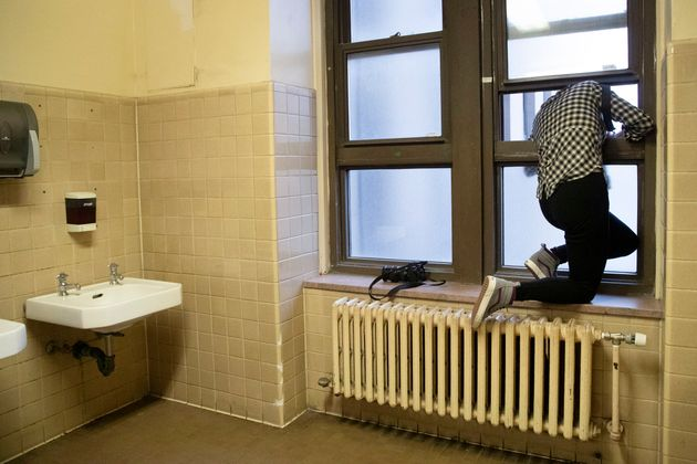 Freelance photographer working for Reuters Caitlin Ochs uses a window in a women's restroom to shoot...