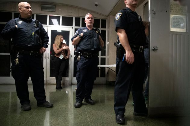 New York Post reporter Rebecca Rosenberg is surrounded by court officers as she stands in the hallway...