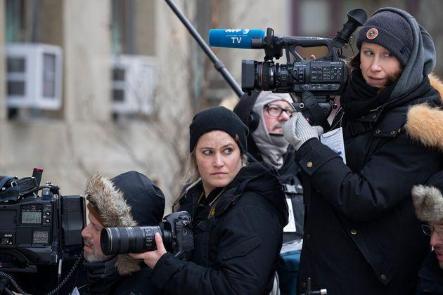 Agence France-Presse photojournalist Angela Weiss, center, and video correspondent Diane Desobeau wait...