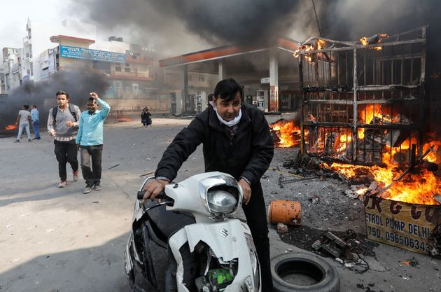 A man pushes his damaged scooter past a burning petrol pump during riots in