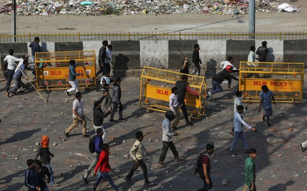 People supporting the new citizenship law and those opposing the law, clash during a protest in New Delhi...