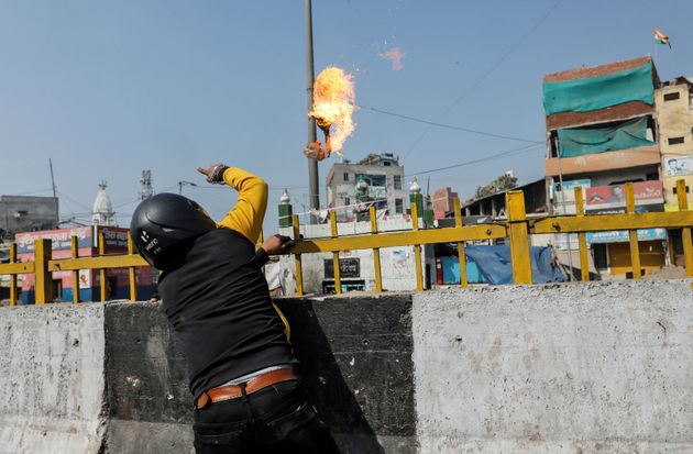 A man throws a petrol bomb at a Muslim shrine during the riots in Delhi on