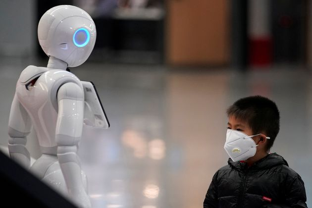 A boy wears a mask watching a robot at the Pudong International Airport in Shanghai, China January 27,...