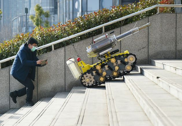 A robotic disinfectant sprayer for preventing the novel coronavirus climbs steps in Luoyang, Henan province,...