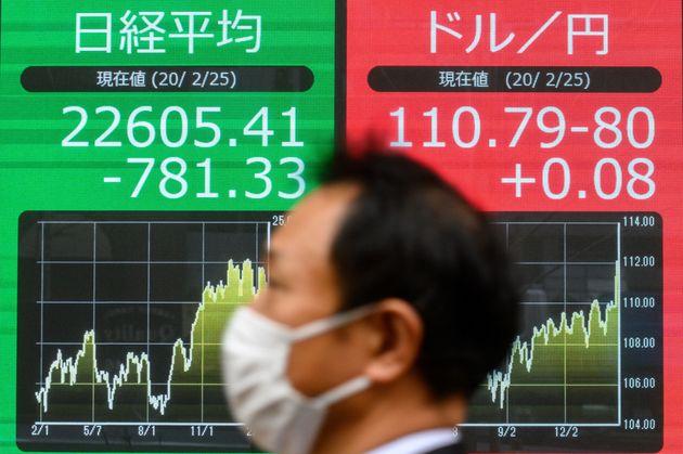 Un peatón con una mascarilla pasa junto a una pantalla de las cotizaciones del índice bursátil Nikkei...