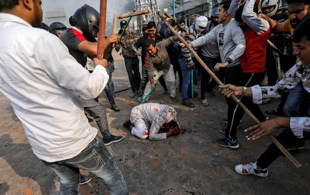 Trigger warning: CAA supporters beat a Muslim man during riots in Delhi on Monday. REUTERS/Danish Siddiqui