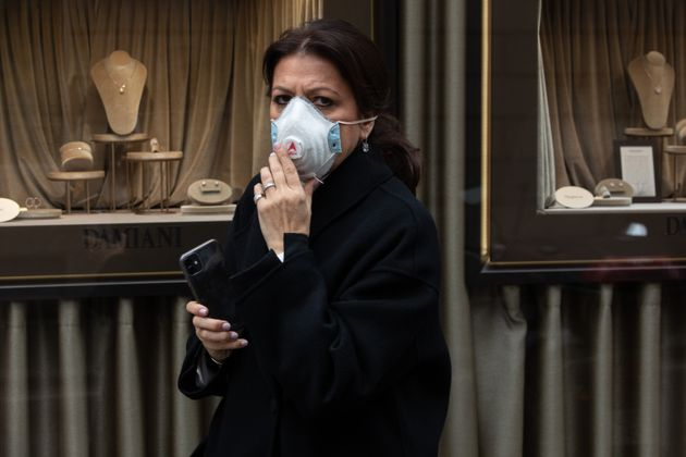 MILAN, ITALY - FEBRUARY 25: A woman, wearing a respiratory mask, walks past a jewelry window in Via Montenapoleone,...