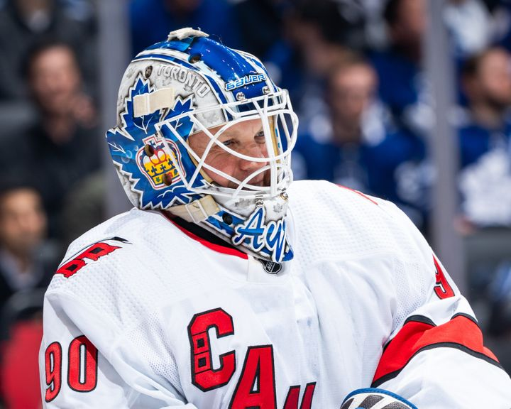 David Ayres smiles through his goalie mask during game action between the Carolina Hurricanes and Toronto Maple Leafs on Saturday in Toronto. The 42-year-old became the oldest goalie in NHL history to win in his debut.