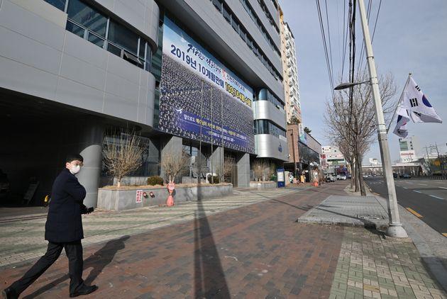 Un homme marchant devant une succursale de l'Église Shincheonji de Jésus à Daegu,...