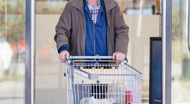 Senior Adult Man Leaving Supermarket and Pushing Shopping