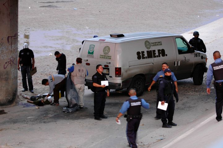 Mexican forensic experts examine the body of SergioHernández under the Paso Del Norte border bridge in the city