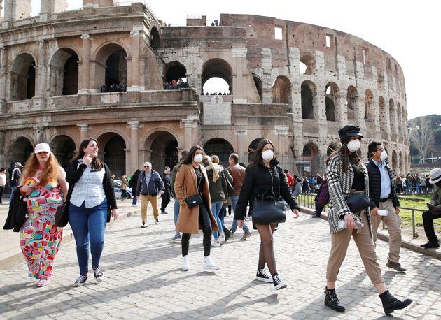 Pessoas usam máscaras ao visitar o Coliseu, em