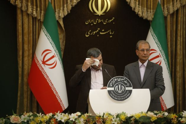 Iraj Harirchi, Iran's deputy health minister, wipes sweat from his face during a news conference on Monday...