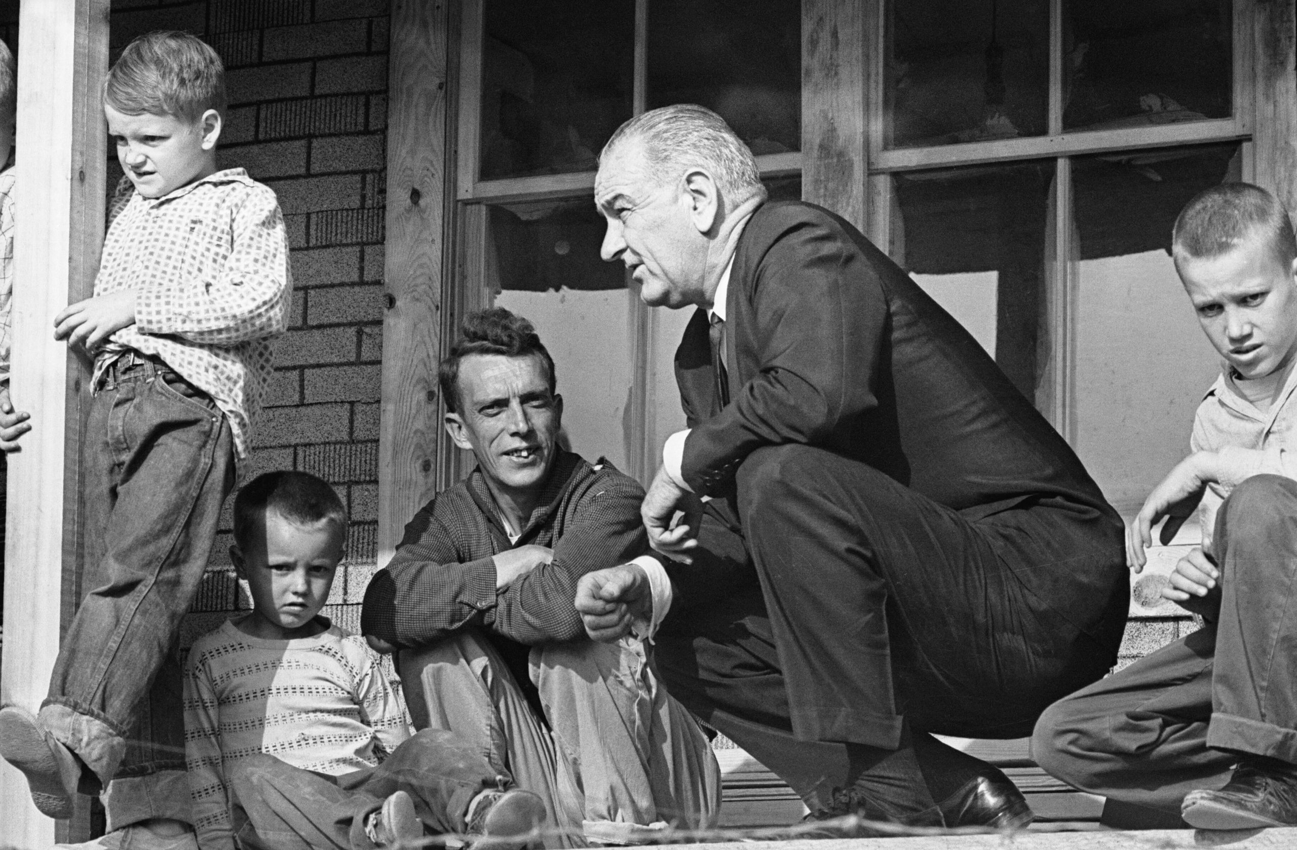 President Lyndon Johnson listens to Tom Fletcher, father of eight, describe some of the problems facing the residents of Inez