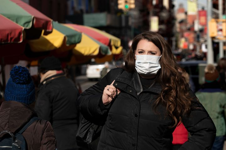 A woman, who declined to give her name, wears a mask out of concern for the coronavirus in New York. Health officials on Tues