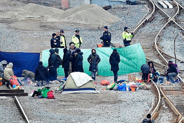 Police speak with protesters camped on GO Transit railroad tracks in Hamilton, Ont., on Feb. 25,