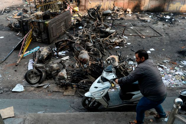 A man makes his way around burnt vehicles after the violence in
