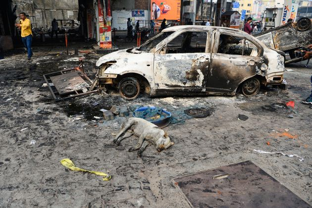 A dog sleeps next to a car after the violence in Delhi on February