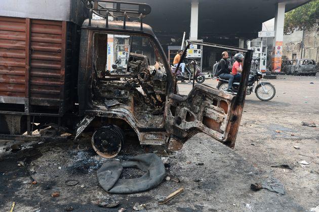 Motorists ride past a burnt