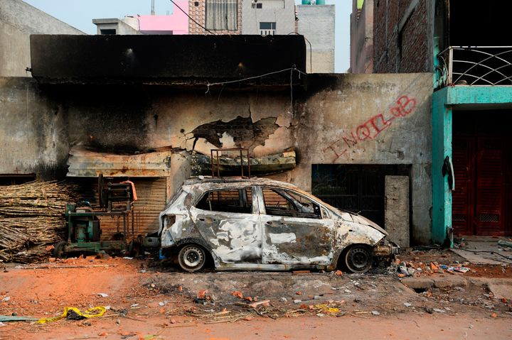 A burnt-out vehicle is pictured following riots in New Delhi, on February 26, 2020.