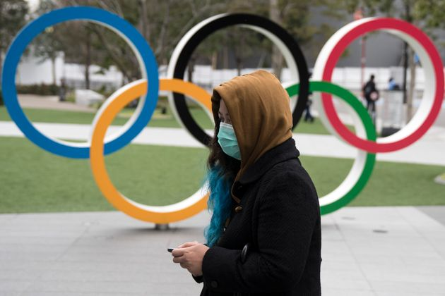 A woman wearing a face mask walks past the Olympic rings in front of the new National Stadium in Tokyo,