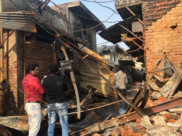 People walk through the destruction left after a fire was started by rioters in Delhi's