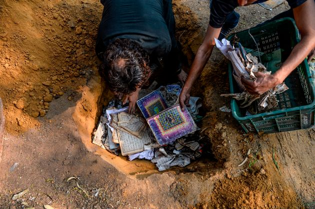 People bury copies of the Koran after they recovered from a burnt mosque on February