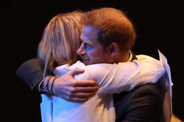 The Duke of Sussex receives a hug as he greets guests at a sustainable tourism summi on Feb. 26, 2020...
