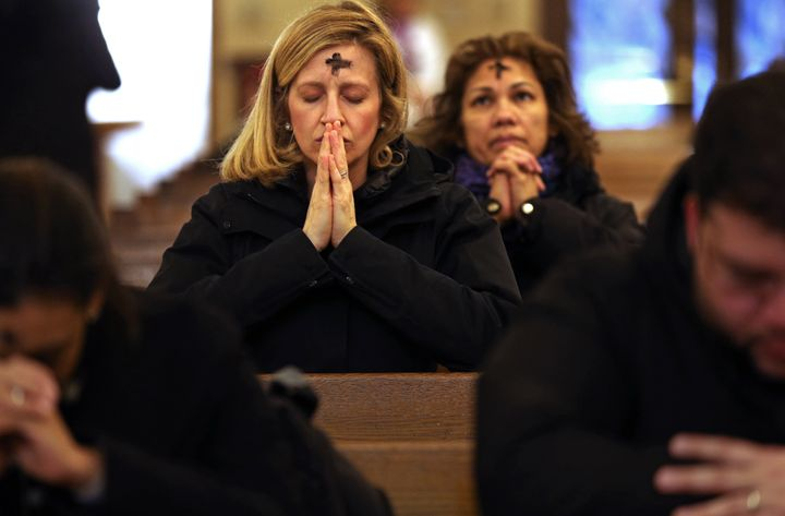 A woman prays after receiving ashes at St. Anthony Shrine in Boston on Ash Wednesday 2018.