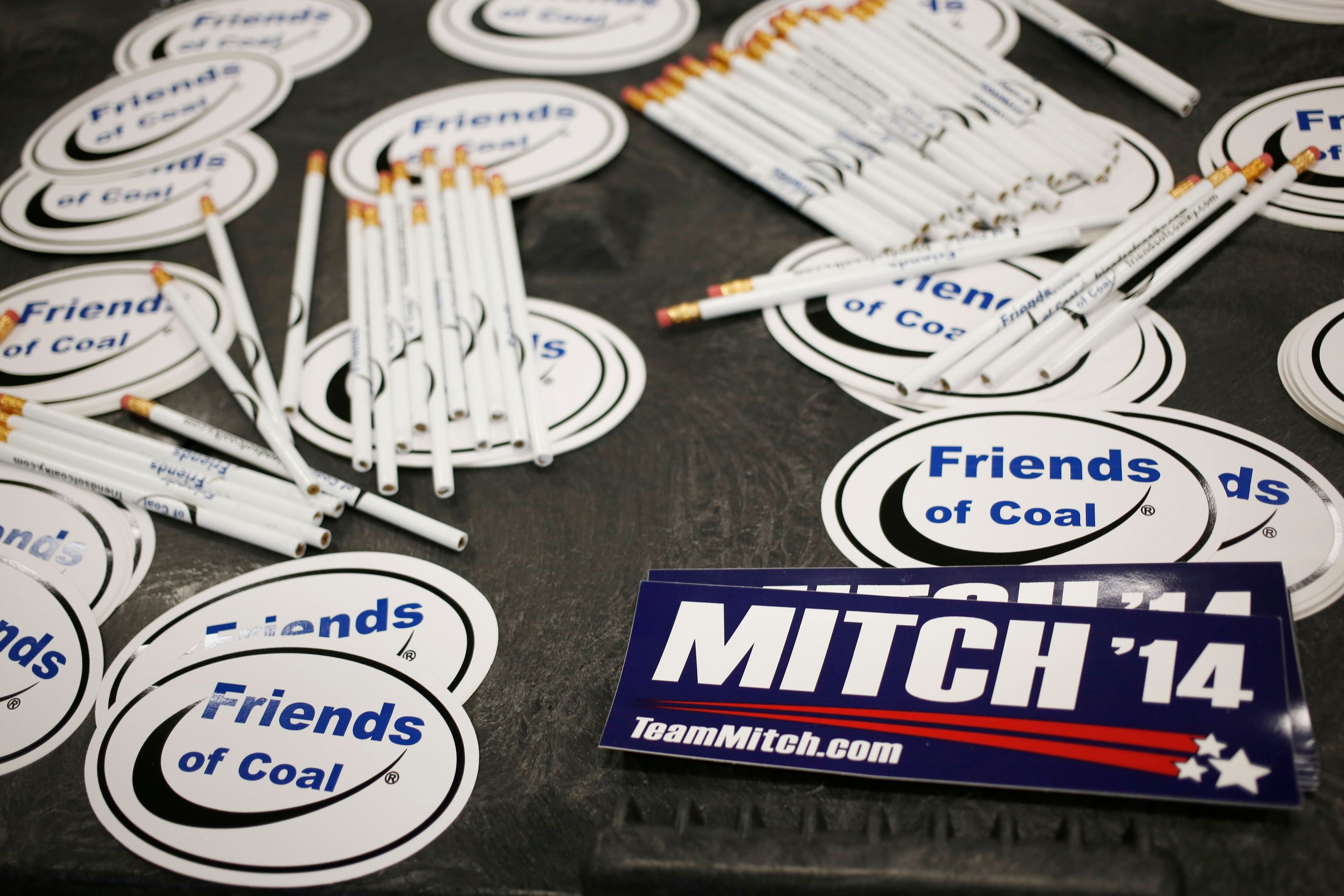 """Bumper stickers for Sen. Mitch McConnell sit on a table alongside """"Friends of Coal"""" advocacy stickers during a campaign stop"""