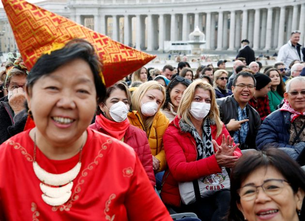 People, a few in face masks, wait for Pope Francis to arrive for his weekly general audience at the