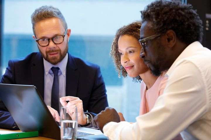 A financial adviser meets with clients in this stock image. It's best to reveal any outstanding debt when getting a mortgage pre-approval as a credit check will uncover them.