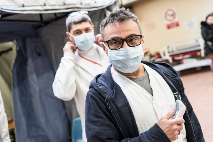 With the exceptions of health-care workers, like these two at the Molinette Hospital in Turin, Italty, and people who are exhibiting symptoms of respiratory illness, face masks are not recommended.
