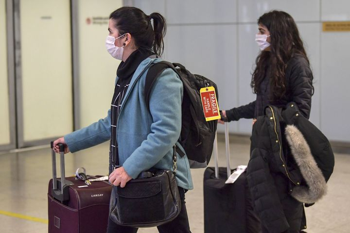 Passengers wear masks as a precautionary measure against the new coronavirus as they travel Wednesday through Guarulhos International Airport in Sao Paulo, Brazil.